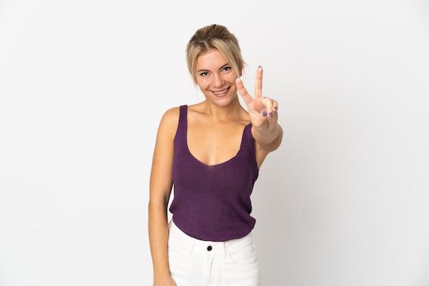 Joven mujer rusa aislada sobre fondo blanco sonriendo y mostrando el signo de la victoria