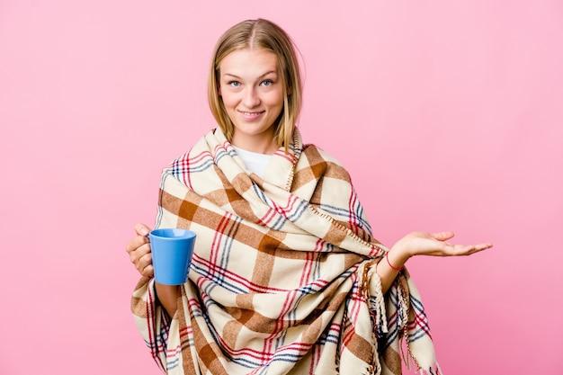 Joven mujer rusa envuelta en una manta tomando café
