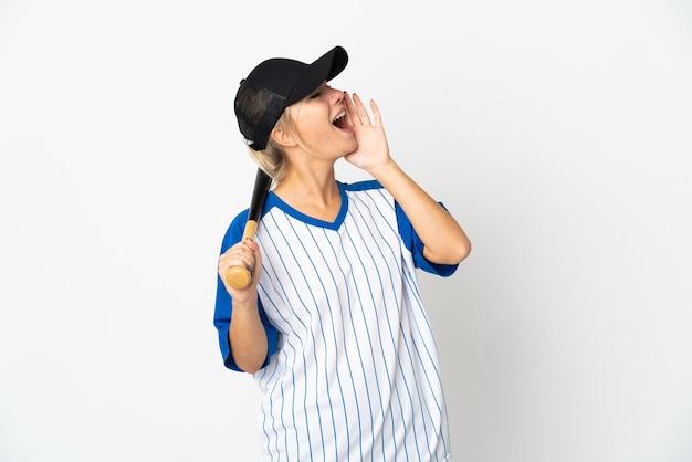 Joven mujer rusa jugando béisbol aislado en la pared blanca gritando con la boca abierta hacia el lado
