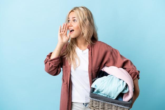 Joven mujer rusa sosteniendo una canasta de ropa aislada en azul gritando con la boca abierta hacia el lado