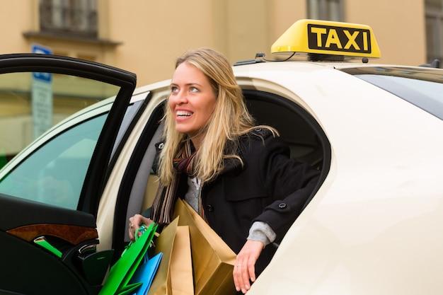 Joven mujer sale del taxi
