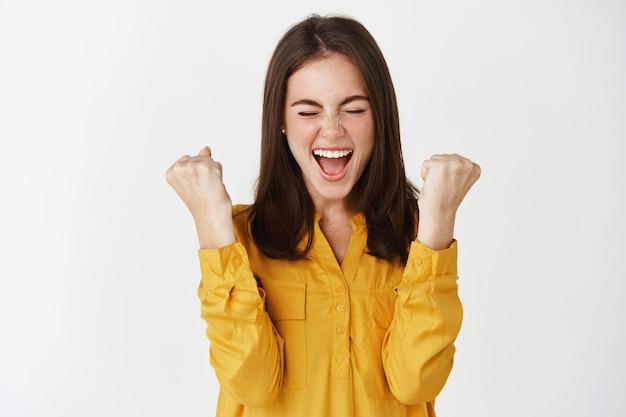 Joven mujer satisfecha ganando el premio y celebrando, haciendo bomba de puño y gritando de alegría, triunfando en la pared blanca