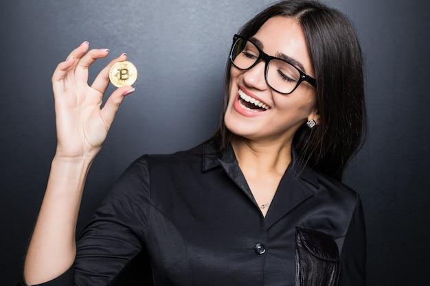 Joven mujer segura de éxito con gafas sostiene un bitcoin de oro en su mano aislado en la pared negra