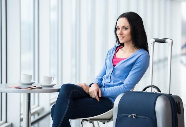 Joven mujer está sentada en el aeropuerto con café.