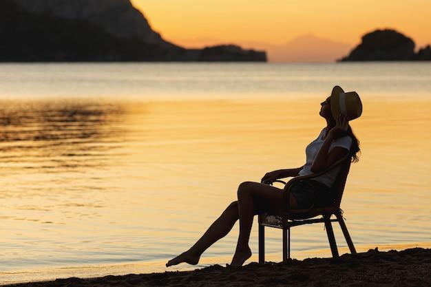 Joven mujer sentada en el asiento en la puesta de sol en la orilla de un lago