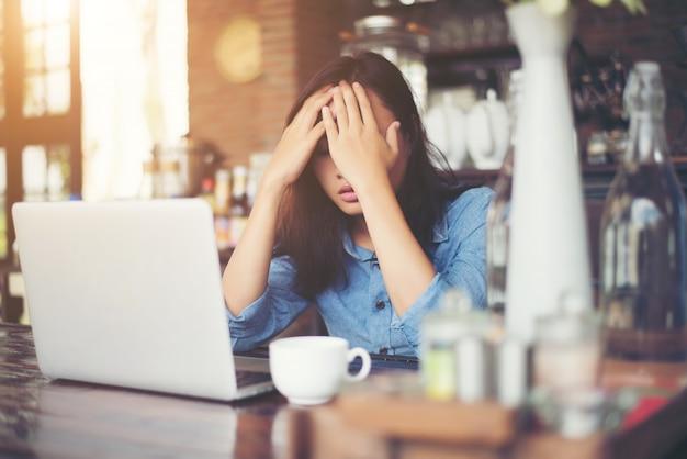 Joven mujer sentada en un café con su portátil, estresante para wor