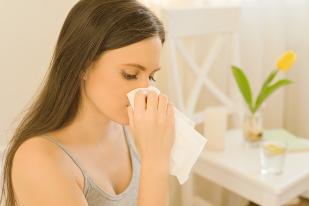 Joven mujer sentada en la cama con pañuelo estornudando