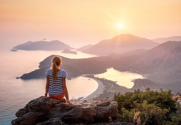 Joven mujer sentada en la cima de la roca y mirando la orilla del mar y las montañas al atardecer colorido en verano