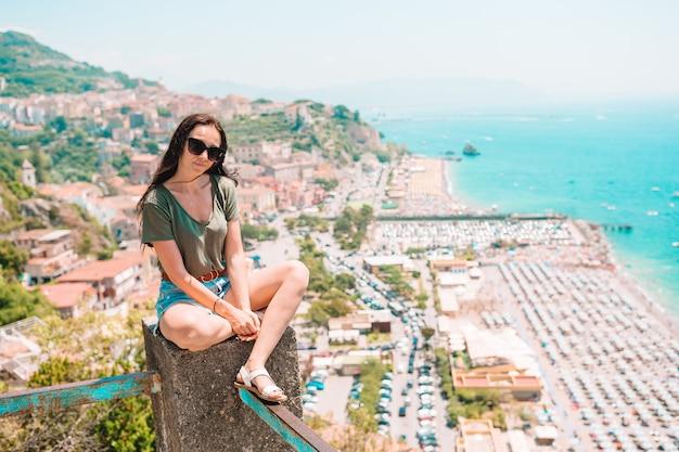 Joven mujer sentada en una glorieta con vistas al mar mediterráneo y la ciudad
