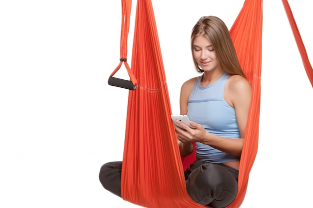 Joven mujer sentada en una hamaca para yoga aéreo antigravedad