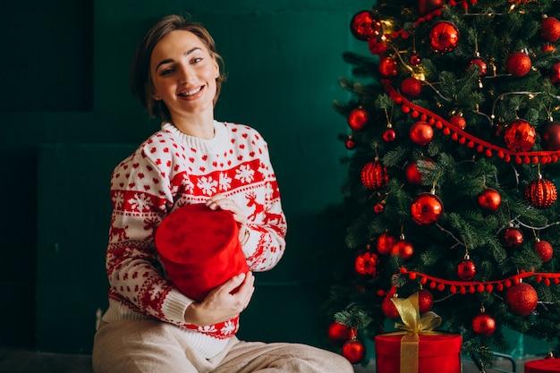 Joven mujer sentada junto al árbol de navidad con cajas rojas