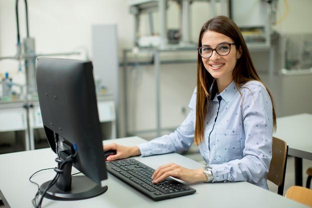 Joven mujer sentada junto al escritorio en el aula