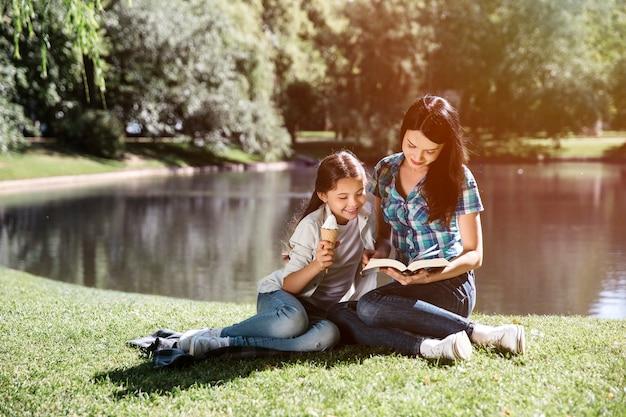 Joven mujer está sentada junto a su hija y leyendo un libro. están mirando el libro juntos. chica se inclina hacia su madre. ella está comiendo helado.