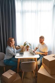 Joven y mujer sentada a la mesa, trabajando en la computadora portátil en la oficina de co-trabajo