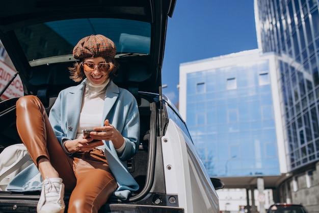 Joven mujer sentada en la parte trasera del coche hablando por teléfono