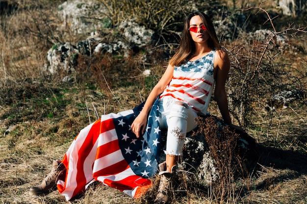 Joven mujer sentada en piedra con bandera
