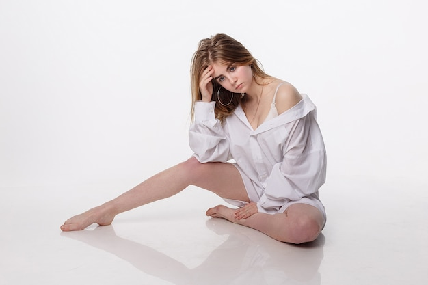 Joven mujer sentada en el piso. linda chica con el pelo largo, inclinando la cabeza sobre las rodillas