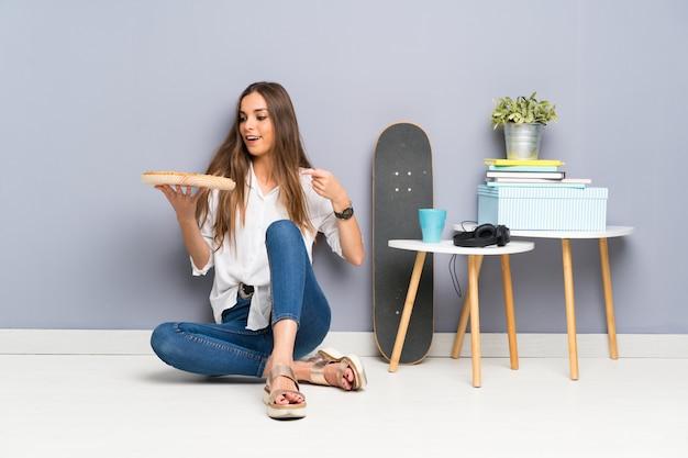 Joven mujer sentada en el piso con una pizza