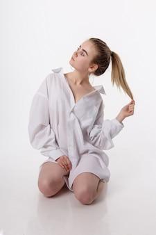 Joven mujer sentada en el piso sobre las rodillas. linda chica con el pelo largo en studio