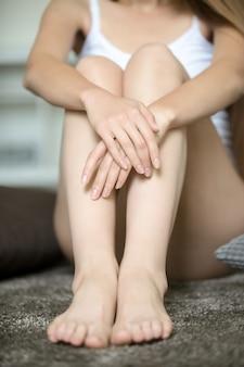 Joven mujer sentada en el suelo, abrazando sus piernas desnudas