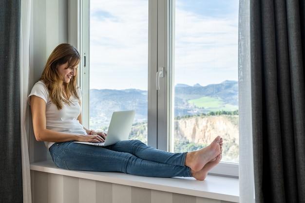 Joven mujer sentada en la ventana trabajando en su computadora portátil