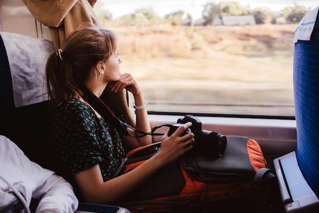 Joven mujer sentada viajando en tren. siéntate solo en la ventana y míralo. la fotógrafa tiene vacaciones o tiempo de vacaciones. viajar al extranjero o dentro de un país.