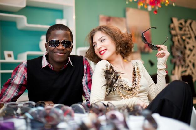 Joven y mujer sentados juntos en la tienda de gafas de sol y sonriendo