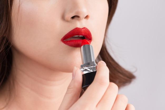 Joven mujer sexy asiática con cabello oscuro con lápiz labial rojo