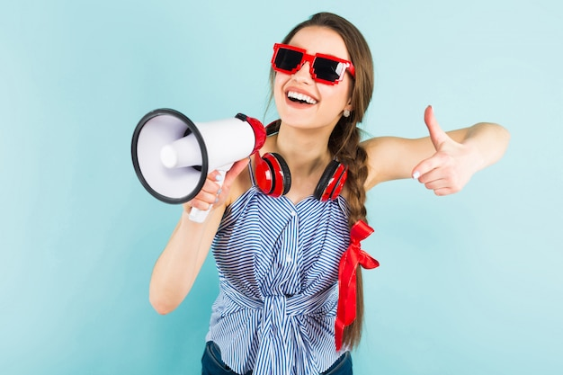 Joven mujer sexy con auriculares y altavoz