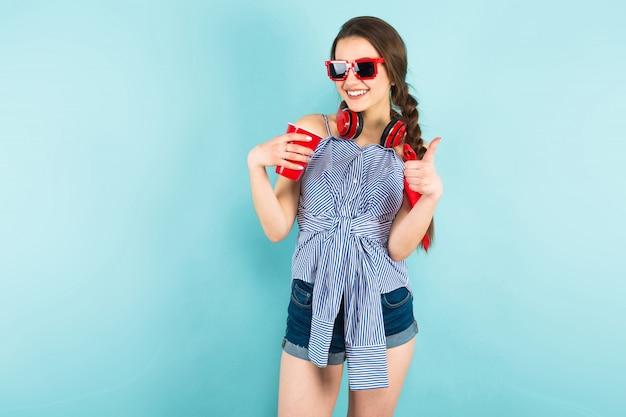 Joven mujer sexy con auriculares y taza