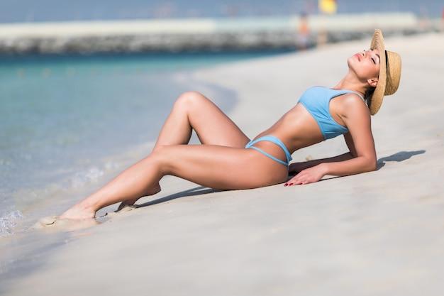 Joven mujer sexy en bikini con sombrero de paja en playa tropical