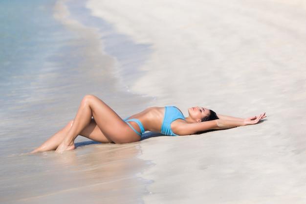 Joven mujer sexy en bikini tumbada en la arena de la costa del océano