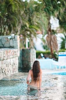 Joven mujer sexy disfrutando de descanso al borde de la piscina al aire libre