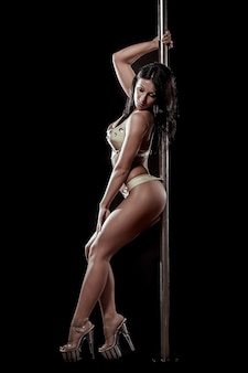 Joven mujer sexy ejercicio pole dance sobre un fondo negro