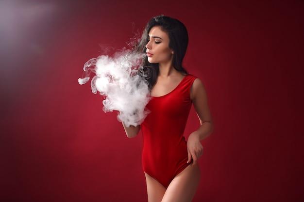 Joven mujer sexy es vaping. una nube de vapor. estudio de rodaje.