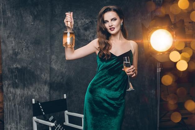 Joven mujer sexy con estilo en el cine entre bastidores, celebrando con una copa de champán