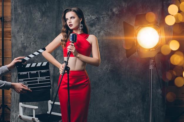 Joven mujer sexy con estilo en el cine entre bastidores, celebrando, vestido de noche de satén rojo, humor de fiesta, estilo de lujo