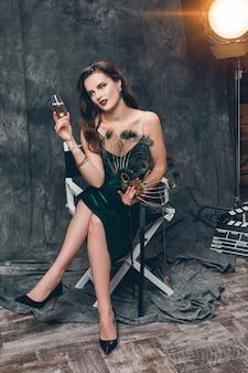Joven mujer sexy con estilo sentado en una silla en el cine entre bastidores, celebrando con una copa de champán