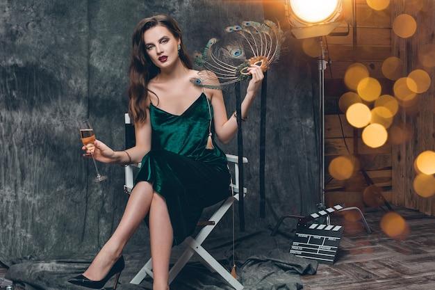 Joven mujer sexy con estilo sentado en una silla en el cine entre bastidores