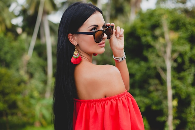 Joven mujer sexy con estilo en vestido rojo de verano de pie en la terraza de un hotel tropical, fondo de palmeras, pelo largo y negro, gafas de sol, pendientes étnicos, gafas de sol, mirando hacia adelante, de cerca