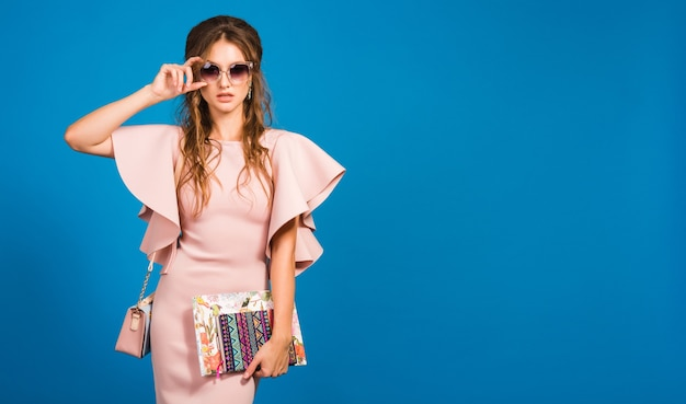 Joven mujer sexy con estilo en vestido rosa de lujo, tendencia de moda de verano, estilo chic, gafas de sol, fondo de estudio azul, bloger de moda