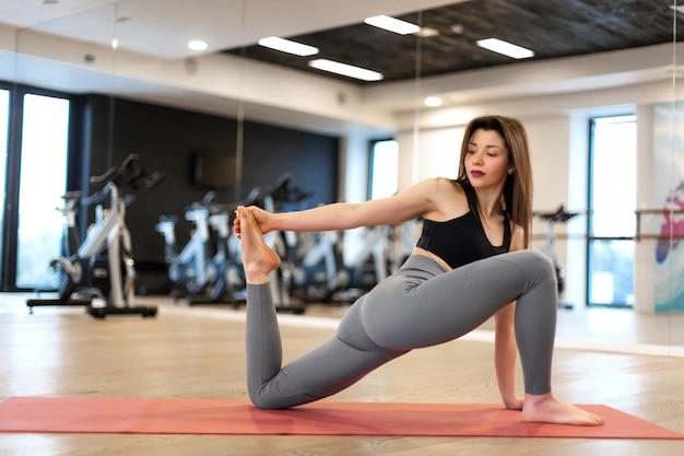 Joven mujer sexy haciendo ejercicios de estiramiento en el gimnasio