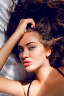 Joven mujer sexy en lencería negra posando en la cama