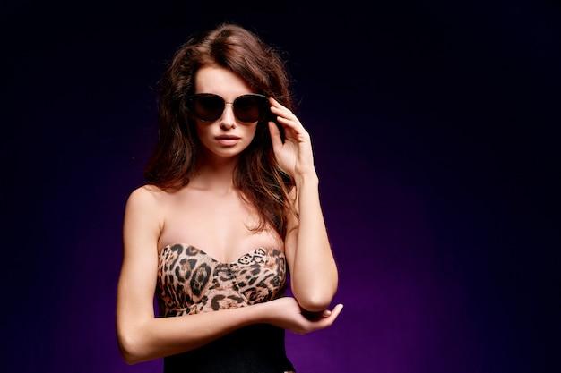 Joven mujer sexy posando en traje de baño de leopardo de moda y gafas de sol con pelo largo en negro