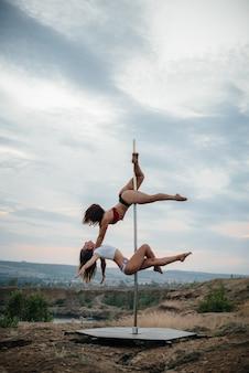 Una joven mujer sexy realiza ejercicios increíbles en un poste durante una hermosa puesta de sol. baile. sexualidad.