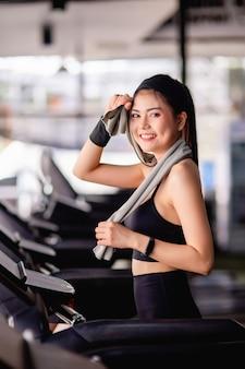 Joven mujer sexy con ropa deportiva, tela a prueba de sudor y reloj inteligente usa una toalla para limpiar el sudor en la frente durante el entrenamiento en el gimnasio moderno, sonrisa, espacio de copia