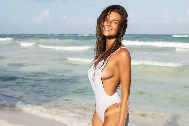 Joven mujer sexy con traje de baño blanco está posando en la playa