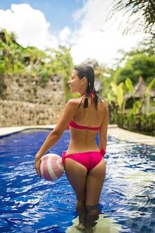 Joven mujer sexy en traje de baño rosa juega con la pelota en la piscina tropical