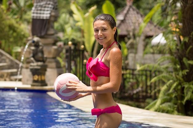 Joven mujer sexy en traje de baño rosa juega con la pelota en la piscina tropical.