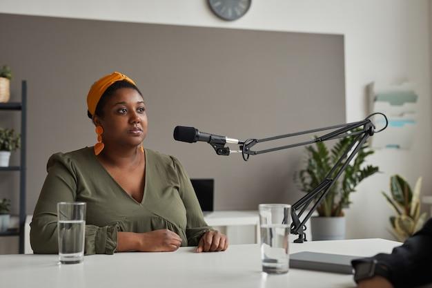 Joven mujer con sobrepeso sentada a la mesa y hablando por micrófono dando una entrevista en la radio